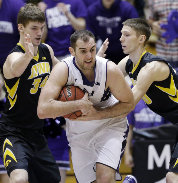 Alex Olah took over down low in the middle of the 2-3 zone, blocking Hawkeye shots and grabbing rebounds, as the Wildcats snapped a 10-game conference losing streak. Photo credit: Quad-City Times.