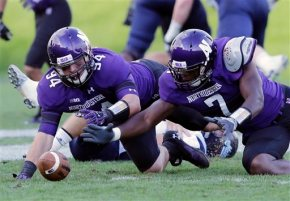 Northwestern defensive lineman Dean Lowry (94) and defensive lineman Ifeadi Odenigbo (7) dive on a fumble by the Maine quarterback Marcus Wasilewski (7)  during the second half of an NCAA college football game in Evanston, Ill., Saturday, Sept. 21, 2013. Northwestern won 35-21. (AP Photo/Nam Y. Huh)